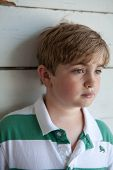 stock photo of pubescent  - Young boy with striped shirt leaning against white wall - JPG