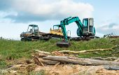 stock photo of truck farm  - Digger and two trucks fitted with tracks used to clear land - JPG