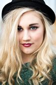 foto of bowler hat  - Portrait of a beautiful confident blond blue eyed teenage girl with long hair wearing a bowler hat green glittery t - JPG
