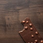stock photo of nibbling  - nibbled chocolate bar with whole hazelnuts on wooden table - JPG