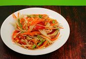 picture of green papaya salad  - thai hot papaya salad with a green background on a wood table top - JPG