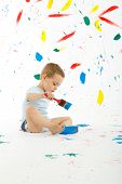 stock photo of floor covering  - Adorable 3 year old boy child creatively stains on the wall floor with colourful paint. Mess of paint on wall floor and everywhere.