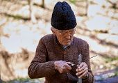 stock photo of man chainsaw  - old man sharpening a chainsaw after work - JPG