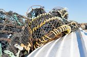 pic of crab  - Lobster and crab pots drying in the sun on the hull of an upturned fishing boat - JPG