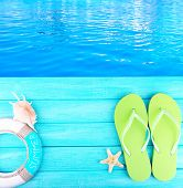 foto of beside  - Colored flip flops on wooden platform beside sea - JPG