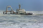 picture of shipwreck  - Shipwreck of a fishing trawler eroding in the waves close to the shore - JPG