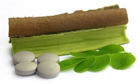 image of malunggay  - Moringa leaves and bark with pills over white background - JPG