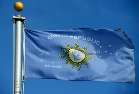 stock photo of conch  - Flag of Conch Republic in blue sky background. Conch Republic was a nation declared by the city of Key West, Florida in 1982 for tourism purpose.  The Flag of Conch Republic is an unofficial flag of all the Florida Keys since then. - JPG