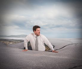 foto of swallow  - Businessman alone and afraid swallowed by asphalt - JPG