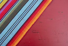 stock photo of mexican fiesta  - Happy Cinco de Mayo background with Mexican style fabric on distressed red wood table - JPG