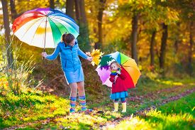 stock photo of rainy season  - Mother and daughter play in autumn park with golden leaves - JPG