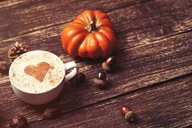 image of cone  - Cup of coffee with heart shape and pine cone with acorn and pumpkin on wooden background - JPG