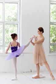 picture of ballet barre  - The little ballerina in tutu with personal classic ballet teacher in dance studio posing at ballet barre on a white background - JPG