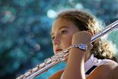 stock photo of piccolo  - girl with a flute listening to her - JPG