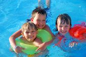 picture of swimming pool family  - Three happy children use flotation devices in a swimming pool - JPG