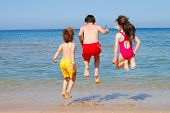 foto of swimming pool family  - Three children jumping into the waves at the beach - JPG
