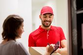 delivery, mail, people and shipping concept - happy man delivering parcel box and customer signing o poster