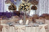 Luxury Wedding Decor With Flowers And Glass Vases And Number  Of Setting On Round Tables. Arrangemen poster