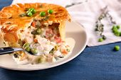 Tasty chicken pot pie with green peas on plate poster