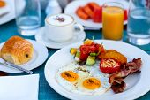 Delicious breakfast with fried eggs, bacon and vegetables poster