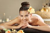 Beautiful young woman lying on massage table in spa salon poster