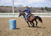 image of barrel racing  - A young blond woman turns around a barrel and races to the finish line - JPG