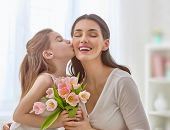 Happy mothers day! Child daughter congratulates mom and gives her flowers tulips. Mum and girl smil poster