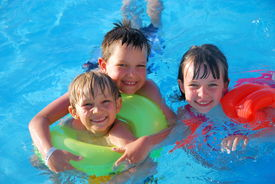 image of swimming pool family  - Three happy children use flotation devices in a swimming pool - JPG