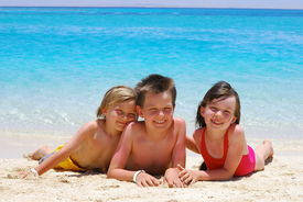 picture of children beach  - Three children laying in the sand at the water - JPG