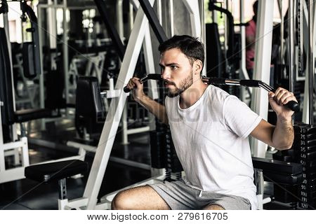 poster of Handsome Man Is Rowing Exercise With Bodybuilder Machine In Fitness Club.,portrait Of Strong Man Doi