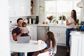Young Hispanic family in their kitchen, dad holding baby, mum cooking at the hob poster