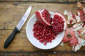 Sliced Pomegranate And Pomegranate Fruits In A White Plate Next To A Knife And A Peel From Pomegrana poster