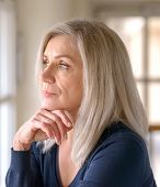 Attractive Thoughtful Woman With Serious Expression Standing With Her Hand To Her Chin Staring Quiet poster