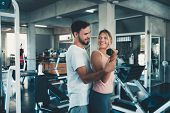 Sporty Couple Exercising Dumbbell Weights Lifting In Fitness Gym., Portrait Of Attractive Young Coup poster
