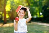 Funny Adorable Little Kid Girl With Book, Apple And Backpack On First Day To School Or Nursery. Chil poster