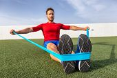 Fitness man training arms with resistance bands at outdoor gym or home garden. Body workout with equ poster