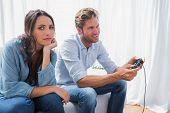 Upset woman annoyed that her partner is playing video games at home on the couch