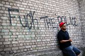 picture of thug  - Young black thug standing on the corner at the dirty brick wall with a sign  - JPG