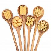 Pasta selection of penne, gnocci, rigatoni, casarecce, fiorelli and algar in wooden spoons over whit