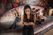 stock photo of cynicism  - Beautiful Hispanic female teenager using cell phone - JPG
