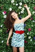 pic of loach  - Beautiful dreaming woman with curly hair stands next to green hedge in garden and looks up - JPG