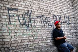 stock photo of fuck  - Young black thug standing on the corner at the dirty brick wall with a sign  - JPG
