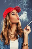 picture of exhale  - Young woman smoking cigarette on a blue background - JPG