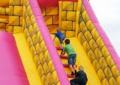 image of inflatable slide  - Children climb steps in inflatable bumper castle - JPG