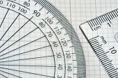 image of protractor  - plastic protractor with triangle over graph paper - JPG