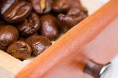 foto of wooden box from coffee mill  - Grains of black roasted coffee in drawer of mill - JPG
