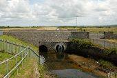 foto of marshlands  - A river flows from marshland through a pair of tunnels under a stone bridge - JPG