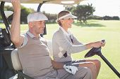 foto of buggy  - Happy golfing couple smiling in their buggy on a sunny day at the golf course - JPG