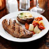 stock photo of braai  - grilled steak with potatoes and stuffed mushroom - JPG
