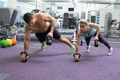 stock photo of bodybuilder  - Bodybuilding man and woman lifting kettlebells in plank position at the gym - JPG